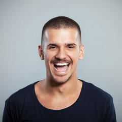 Close-up of a young man laughing. Studio Shot.