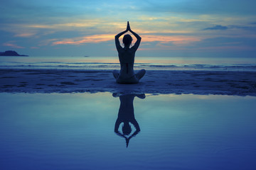 Yoga girl on sea beach after sunset with reflection in water.