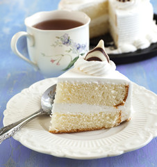 Piece of cake on plate and cup of tea