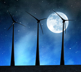 Wind turbines in the night sky with moon.