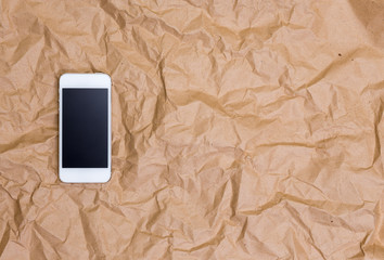 Mobile phone on crumpled paper background