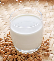 Soy milk and beans on wood background