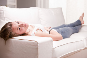girl looking you and smiling while lying on a sofa