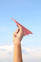 Hand holding pink paper aeroplane