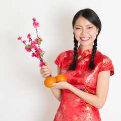 Asian chinese girl holding tangerine and plum blossom