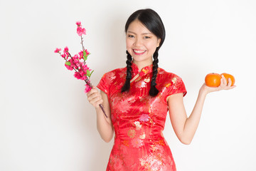 Asian chinese girl holding tangerine orange and plum blossom