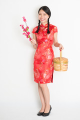 Asian chinese girl holding gift basket and plum blossom