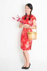 Chinese girl holding gift basket and plum blossom