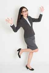 Full body cheering Asian business woman