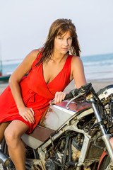 Sexy girl  in red dress on motorcycle