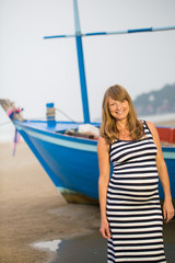 Beautiful pregnant woman relaxing outside on the beach