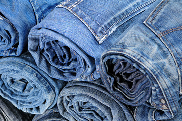 Stack of rolled colored jeans. Top view
