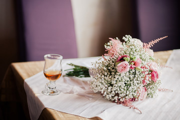 wedding bouquet  and  a cup of tea on the table