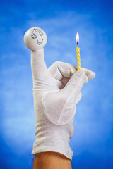 Burning birthday candle hold by finger puppet