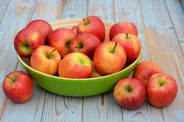 Verse appels in groene fruitschaal op oud hout