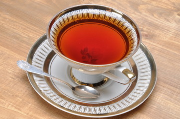 Tea in old cup on wooden board