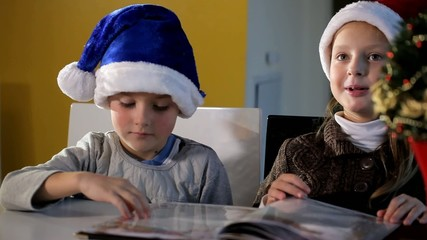 Boy and girl in a Santa Claus hat flipping book