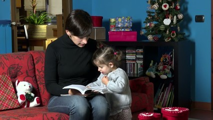 Happy mother reading book to daughter for Christmas at home