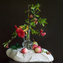 flowers, pomegranate, and apples on a stone
