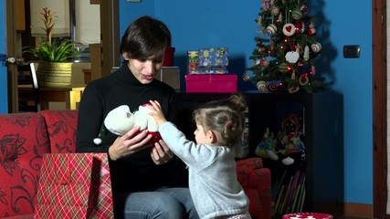Mother and child open Christmas present gift during holidays