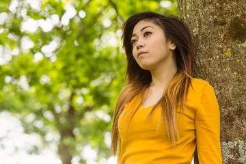 Beautiful woman against tree in park