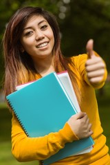 Female college student with books gesturing thumbs up in park