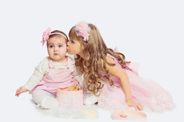 Adorable little sister hugging and kissing her baby sister