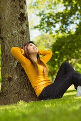 Beautiful woman sitting against tree in park