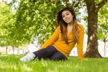 Beautiful relaxed woman sitting on grass at park