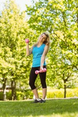 Fit blonde lifting dumbbells in the park