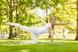 Fit blonde doing yoga in the park - 74713742