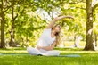 Fit blonde doing yoga in the park - 74713757