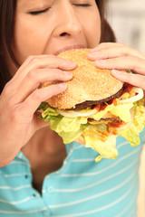 Frau beißt genüsslich in einen Burger