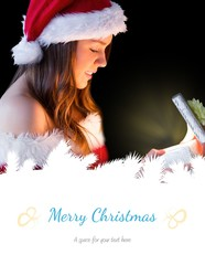 Composite image of pretty brunette in santa outfit opening gift