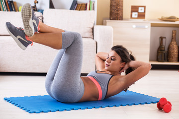 Attractive female exercise at home.Fitness.Doing abs.