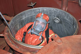 man in chemical suit entering inside cargo tank