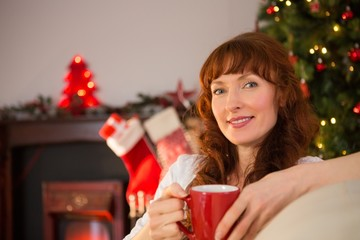 Smiling redhead holding a mug of hot drink at christmas