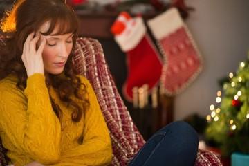 Unhappy redhead getting a headache at christmas