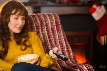 Pretty redhead watching television on couch at christmas