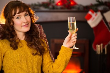 Redhead holding glass of champagne on couch at christmas