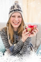 Happy blonde in winter hat sitting on couch showing a gift