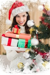 Festive brunette holding pile of gifts near a christmas tree