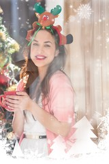 Composite image of brunette in christmas hat holding mug