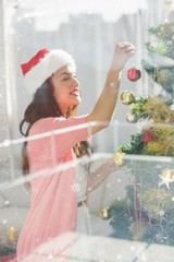 Composite image of festive brunette decorating a christmas tree
