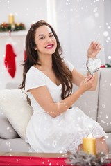 Composite image of happy brunette holding heart for decoration