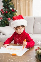 Composite image of festive little boy writing wish list