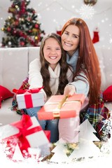 Festive mother and daughter wrapped in blanket with gifts