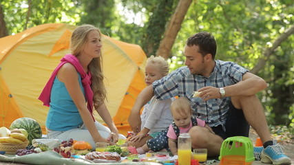 Beautiful family eats on the nature having a picnic in the