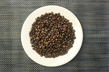 White round plate with a heap of coffee beans