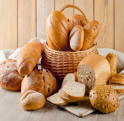 Different bread in basket on a wooden background